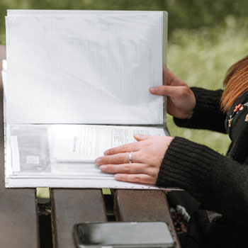 Woman reviewing papers outdoors