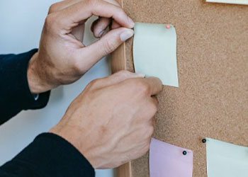 A person filling his board with sticky notes