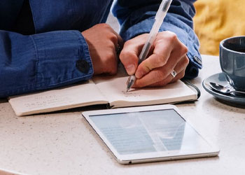A man writing on a notebook while using his ipad