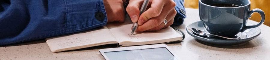 A man writing inside a coffee shop