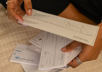 A woman holding out envelopes and letters