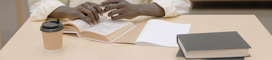 black man studying with books in a library