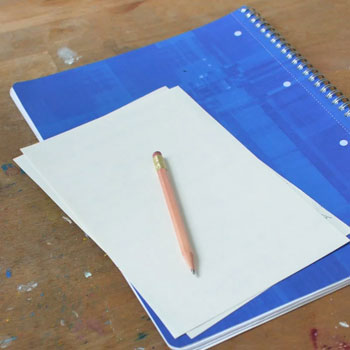 A pencil and notebook on a table