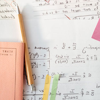 A notebook and pencil with a sketchpad full of math solutions