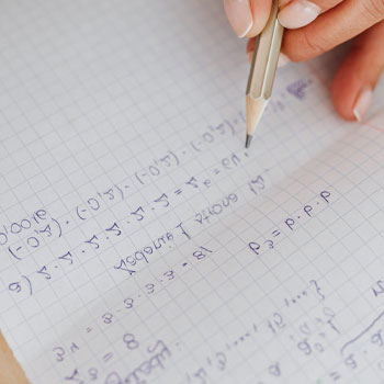 A man calculating on a piece of paper without a calculator on GMAT exam