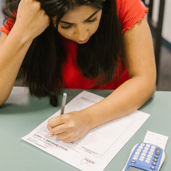 A stressed woman taking an exam in a classroom