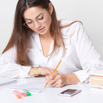A woman writing on a paper sitting down