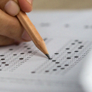 A hand holding a pencil and shading the SAT answer sheet