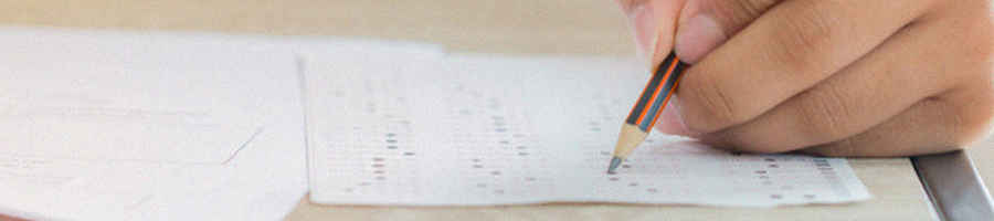 A person answering multiple GRE answer sheets