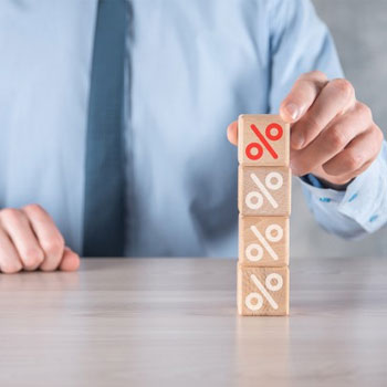 A man stacking small blocks with percentile symbols