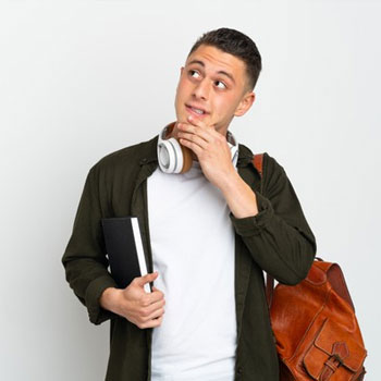 Male student carrying his backpack and books while thinking