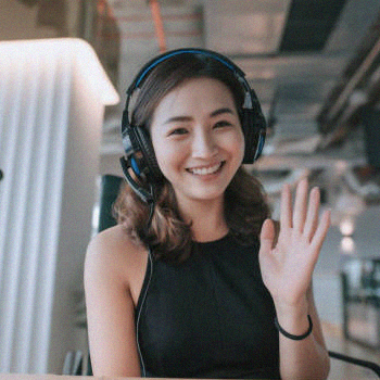 A student waving in front of the camera