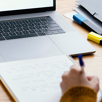 A person writing notes in front of a laptop