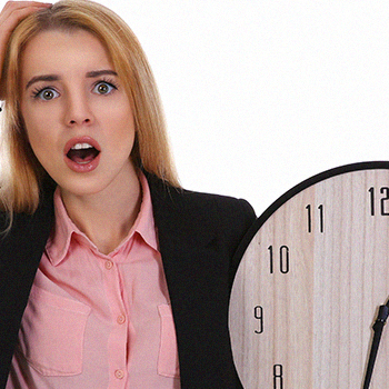 A woman in a suit holding a big clock
