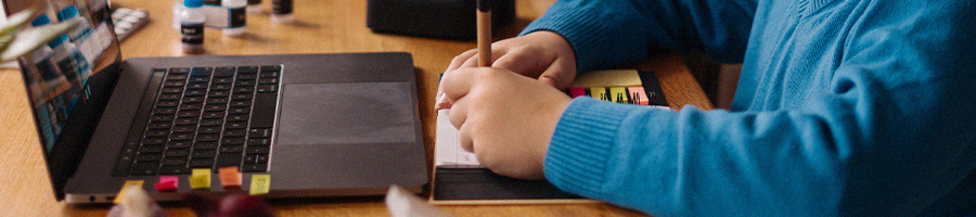 A student writing a note during online class