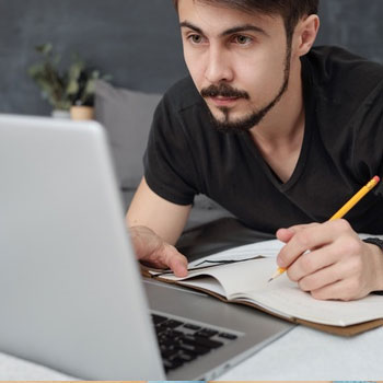 male person writing on a notebook while reading on a laptop