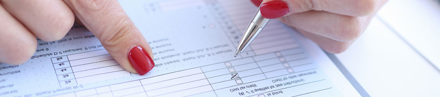 Woman with red nails filling up a paper form