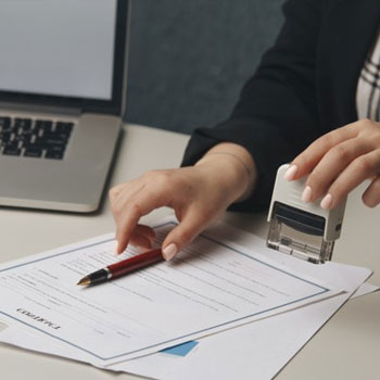 person stamping and signing a paper