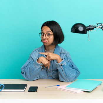 female student pointing at her wrist seated on desk