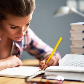 woman writing on a notebook with stack of books open