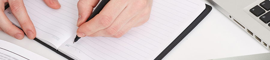 Top view of someone writing on a notebook