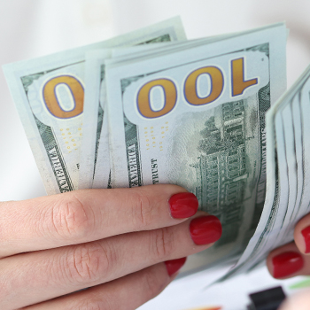 A woman with red nails holding cash