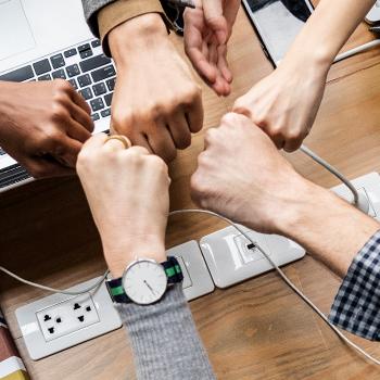 A group fist bumps symbolizing teamwork