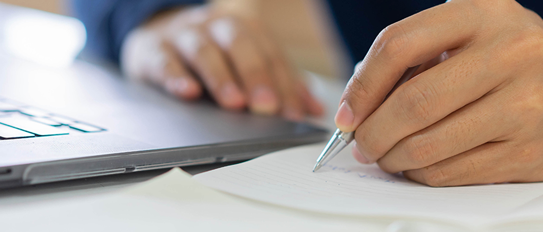 A man writing on a notebook for his GRE verbal prep