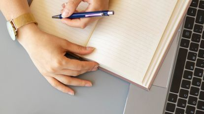 A person writing down questions