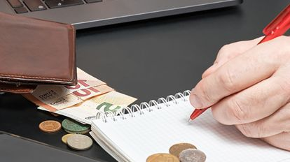 A person writing the costs and expenses for online class