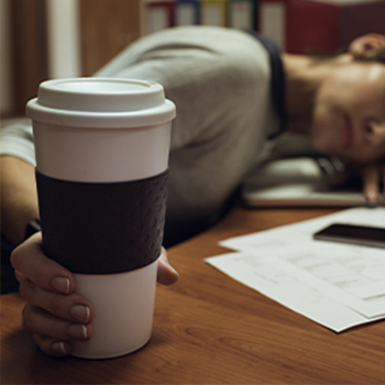 An exhausted person from her workload while still holding her coffee