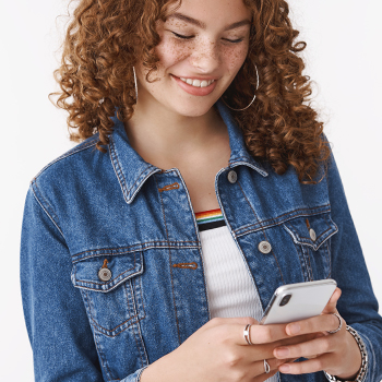 A woman smiling scrolling through her phone