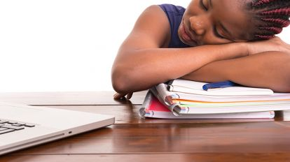 A student tired of studying, resting her head on a pile of books in front of her laptop