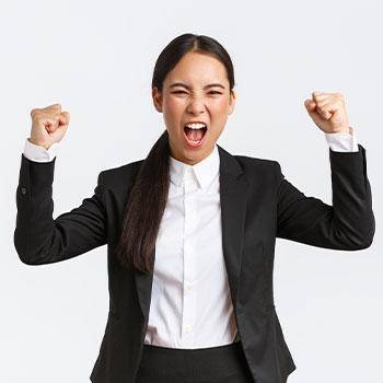Female in corporate attire throwing her hands in joy